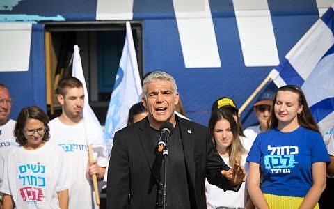 Yair Lapid and supporters of Blue and White Party pose outside their campaign bus in Glilot, July 21, 2019. (Flash90)