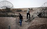 Palestinians illegally crossing the Israeli security fence through a hole to enter Israel on the outskirts of the West Bank city of Hebron, on August 6, 2019. (Wisam Hashlamoun/Flash90)