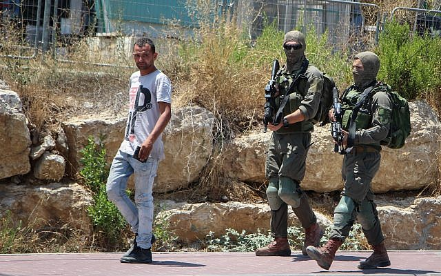 Israeli soldiers are seen near the West Bank settlement of Migdal Oz, on August 8, 2019, after seminary student Dvir Sorek was found stabbed to death outside the settlement. (Gershon Elinson/Flash90)