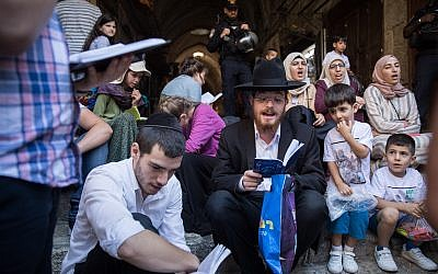 Jews pray as Muslims yell in Arabic God is Great outside the Temple Mount in the Old City of Jerusalem on August 11, 2019. (Hadas Parush/Flash90)