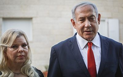 Prime Minister Benjamin Netayahu and his wife Sara speak with the media outside the Sorek family home, in Ofra, in the West Bank on August 13, 2019. (Flash90)