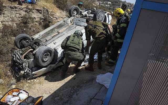 Soldiers inspect a car used in a ramming attack outside the West Bank settlement of Elazar on August 16, 2019 (Gershon Elinson/Flash90)