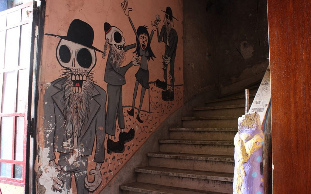 Anti-Semitic caricatures of dead Jews assaulting a woman are drawn onto the walls of the newly-reclaimed synagogue in Buenos Aires that for years had housed raves thrown by squatters. (Daniel Silicaro)