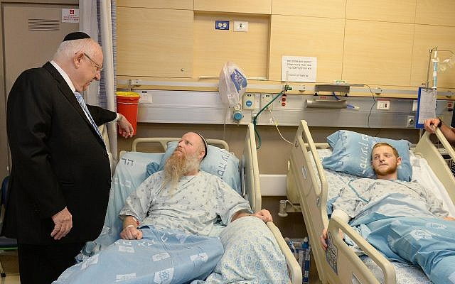 President Reuven Rivlin visits Rabbi Eitan Shnerb, whose daughter Rina was killed in a West Bank terror bombing, and his son Dvir at Hadassah Hospital Ein Kerem in Jerusalem on August 26, 2019. (Mark Neiman/GPO)