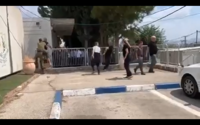 A scuffle breaks out outside the Samaria Military Court in the northern West Bank on August 7, 2019, after Amjad Na'alowa is convicted of failing to prevent his brother Ashraf's deadly terror attack in the Barkan Industrial Park last year. (Screenshot)