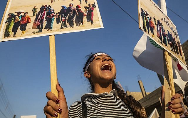 A Syrian Yazidi girl marches with pictures during a demonstration in the northeastern town of Amude, about 28 kilometers west of Qamishli near the Syrian-Turkish border, on August 3, 2018, commemorating the fifth anniversary of the Islamic State (IS) group's attacks in the Sinjar mountains in Iraq's Yazidi heartland. (Delil Souleiman/AFP)