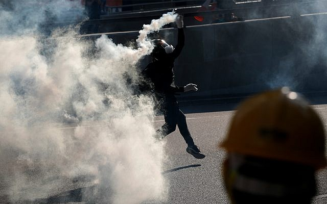 A protester throws a tear gas canister fired by riot police as they face off near the Legislative Council building and the Central Government building in Hong Kong, Monday, August 5, 2019. (AP Photo/Vincent Thian)