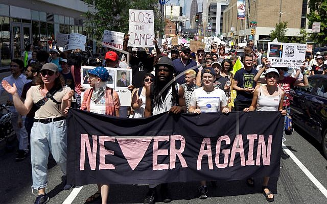 Protesters assembled by a majority Jewish group called Never Again Is Now walk through traffic as they make their way to Independence Mall in Philadelphia, July 4, 2019. (AP Photo/Jacqueline Larma, File)