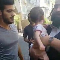 Passersby rescue an infant from a sweltering car in Bnei Brak, August 12, 2019. (Twitter screenshot)