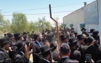 Haredi demonstrators clash with police outside of a warehouse in the southern town of Arad on August 11, 2019. (Screen capture/Twitter)