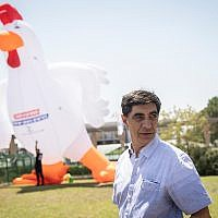 Simcha Goldin, the father of slain IDF soldier Hadar Goldin, stands with a 10 meter (32 foot) tall inflatable rooster at a demonstration outside the Knesset on August 14, 2019. (Hadas Parush/Flash90)