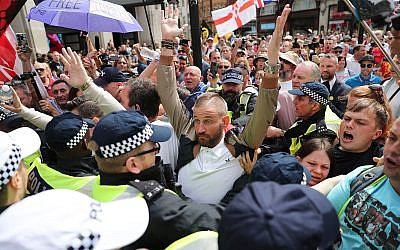Supporters of far-right activist Stephen Yaxley-Lennon, known as Tommy Robinson, are restrained by police, in Oxford Street, London, Aug. 3, 2019. (Steve Parsons/PA via AP)
