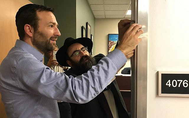 California State Senatpr Ben Allen, chair of the Jewish Caucus, puts a mezuzah on his office door with Rabbi Mendy Cohen. (Courtesy of the Jewish Caucus via JTA)