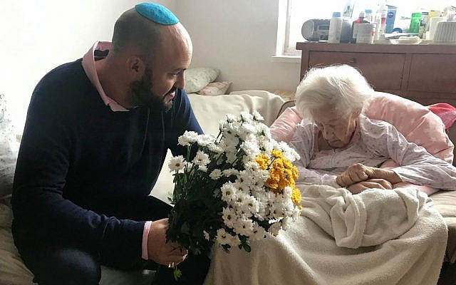 Illustrative: Krystyna Danko receives flowers from From the Depths founder Jonny Daniels in her Warsaw apartment on her 102nd birthday, July 9, 2019. (From the Depths via JTA)