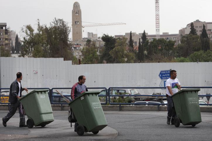 Three men each pushing a green garbage bin walk in Jerusalem on October 27, 2009. (Nati Shohat/FLASH90)