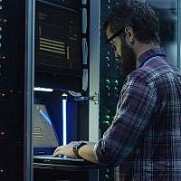 Illustrative: An IT worker stands in a server farm (Evgeniy Shkolenko; iStock by Getty Images)