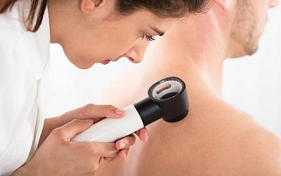 Illustrative image of a doctor using a dermatoscope for a skin examination for melanoma (AndreyPopov, iStock by Getty Images)