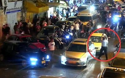 A police officer (marked by red circle) fires in the air to scatter several young men attacking a Jewish driver on Salah Ad-Din Street in East Jerusalem, August 11, 2019. (Israel Police video)