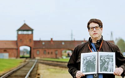 Times of Israel reporter Matt Lebovic at Auschwitz-Birkenau holding a version of 'The Auschwitz Album' image in which his grandmother, Bella (Baila) Solomon, appears, October 2017 (Elan Kawesch/The Times of Israel)