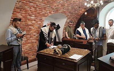 Rabbi Shimshon Izakson, second from left, praying with congregants at the Wooden Synagogue in Chisinau, Moldova on August 26, 2019. (Cnaan Liphshiz/JTA)