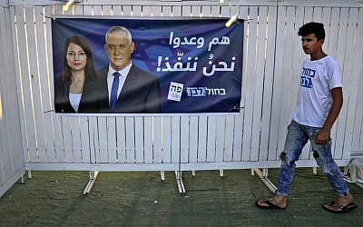 An Arabic-language campaign poster of Blue and White party leader Benny Gantz and MK Gadeer Mreeh is seen outside a campaign event in Shfaram on August 26, 2019. (Ahmad Gharabli/AFP)