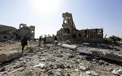People inspect the rubble of a destroyed building that was used as a detention center by Yemen's Houthi rebels which was hit by an air strike by the Saudi-led coalition, in Dhamar south of the Houthi-held capital Sanaa on September 1, 2019. (AFP)