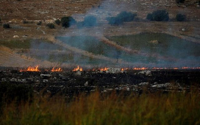 Fires and smoke rising, after the Hezbollah terror group fired anti-tank missiles toward Israel, as seen from a location near the northern moshav of Avivim, close to the border with Lebanon, on September 1, 2019. (Jalaa Marey/AFP)