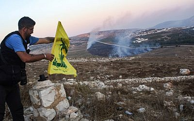 A man fixes a Hezbollah flag at the 'Garden of Iran' Park in the Lebanese village of Maroun al-Ras on September 1, 2019, as fires blaze on the Lebanese side along the border following an exchange of fire with Israel. (Mahmoud Zayyat/AFP)