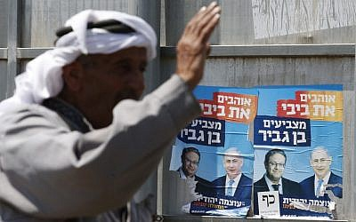 A Palestinian gestures next to campaign posters depicting Prime Minister Benjamin Netanyahu and far-right candidate Itamar Ben Gvir (L) in the West Bank town of Hebron on September 7, 2019. (HAZEM BADER / AFP)