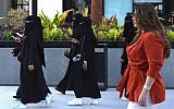 Saudi human resources professional Mashael al-Jaloud, right, walks in Western clothes past women wearing niqabs and abayas, an Islamic dress-code for women, at a commercial area in the Saudi capital Riyadh on September 3, 2019. (Fayez Nureldine/AFP)