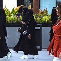 Saudi human resources professional Mashael al-Jaloud, right, walks in Western clothes past women wearing niqab and abaya, an Islamic dress-code for women, at a commercial area in the Saudi capital Riyadh on September 3, 2019. (FAYEZ NURELDINE / AFP)