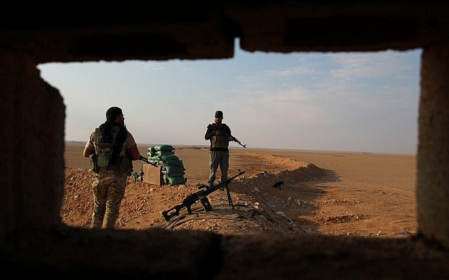 Iraqi Shiite fighters of the Popular Mobilization Forces secure the border area with Syria in al-Qaim in Iraq's Anbar province, opposite Al-Bukamal in Syria's Deir Ezzor region, on November 12, 2018. (Photo by AHMAD AL-RUBAYE / AFP)
