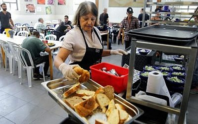A Lasova restaurant soup kitchen employee serves bread to the needy in the Israeli coastal city of Tel Aviv on September 8, 2019. (Menahem Kahana/AFP)