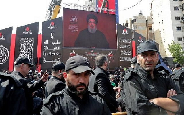 Members of the Lebanese Hezbollah movement's security, stand guard during a religious mourning procession on the tenth day of the lunar month of Muharram, which marks the day of Ashura, in a suburb of the capital Beirut, on September 10, 2019 (ANWAR AMRO / AA / AFP)