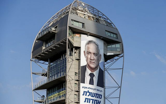 """This picture taken on September 10, 2019 shows an electoral banner for the Blue and White alliance showing the face of retired general Benny Gantz and a caption in Hebrew reading """"only a big Blue and White will create a secular unity government"""" hanging from a building in Tel Aviv. (AHMAD GHARABLI / AFP)"""