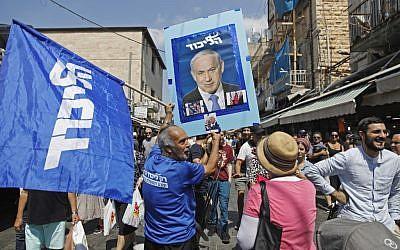 Supporters of Prime Minister Benjamin Netanyahu march at the Mahane Yehuda market in Jerusalem on September 13, 2019. (Menahem Kahana/AFP)