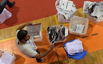 A staff member of Tunisia's Independent Higher Authority for Elections (ISIE) sorts through ballot boxes as they prepare the results of the presidential vote at a sorting center in Ariana, north of the capital Tunis on September 16, 2019 (FETHI BELAID / AFP)