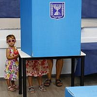 Israeli children accompany their father in a polling booth during Knesset elections at a polling station in Rosh Ha'ayin, on September 17, 2019. (Jack Guez/AFP)