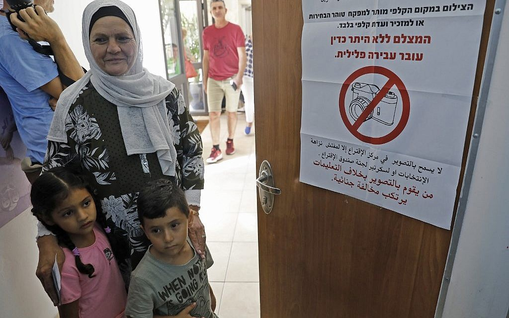 An Arab Israeli woman on election day at a polling station in Haifa,  on September 17, 2019. The sign on the door warns the unauthorized photography is illegal. (Photo by Ahmad GHARABLI / AFP)
