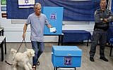 An Israeli man holds his dog while casting his ballot at a polling station in Rosh Haayin, on September 17, 2019. (Jack GUEZ / AFP)