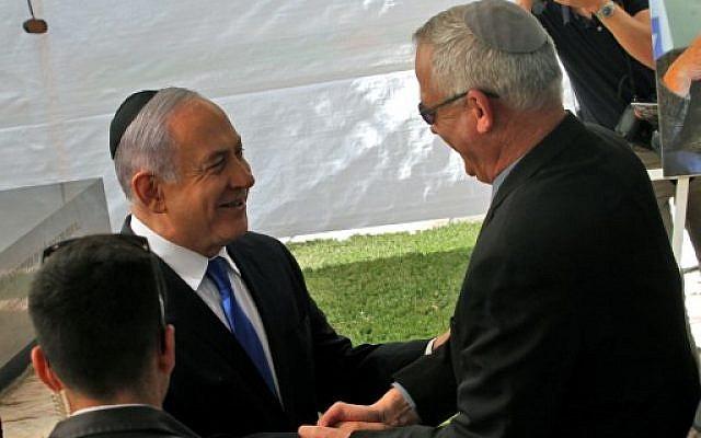 Prime Minister Benjamin Netanyahu (L) greets Benny Gantz, leader of Blue and White party, at a memorial ceremony for late Israeli president Shimon Peres, at Mount Herzl in Jerusalem on September 19, 2019. (Gil Cohen-Magen/AFP)