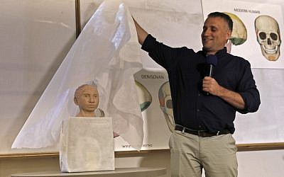 Liran Carmel of the Hebrew University reveals a 3D printed model of the face of prehistoric human species Denisovan during a press conference at the Hebrew University in Jerusalem on September 19, 2019. (MENAHEM KAHANA / AFP)