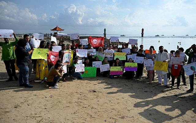 People display placards during a rally as part of a global climate change campaign at Sanur beach on Indonesia's resort island of Bali on September 20, 2019. (SONNY TUMBELAKA / AFP)