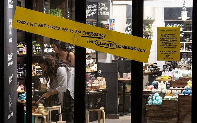 """In this picture taken on September 19, 2019, employees arrange a display behind a sign warning customers of a """"climate strike"""" closure of a skin care shop in Singapore on September 20, as part of a global climate change campaign. (Mladen ANTONOV / AFP)"""