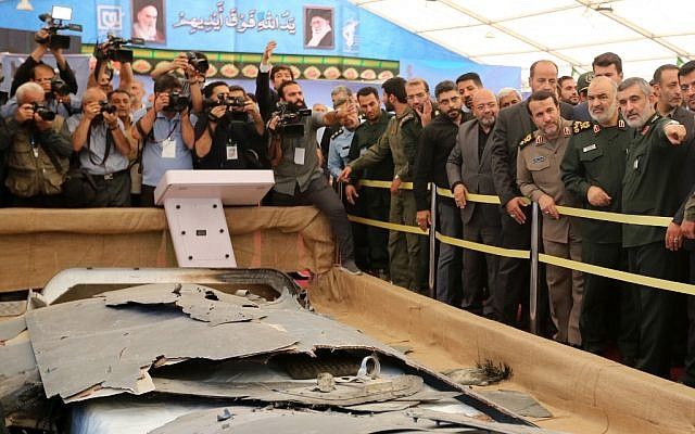 Iranian Revolutionary Guards commander Maj. Gen. Hossein Salami (2nd-R) and Gen. Amir Ali Hajizadeh (R), head of Iran's Revolutionary Guards aerospace division, looks at debris from what Iran presented as a downed US drone reportedly recovered within Iran's territorial waters, at Tehran's Islamic Revolution and Holy Defense museum, during the unveiling of an exhibition of what Iran says are US and other drones captured in its territory, on September 21, 2019. (Atta Kenare/AFP)
