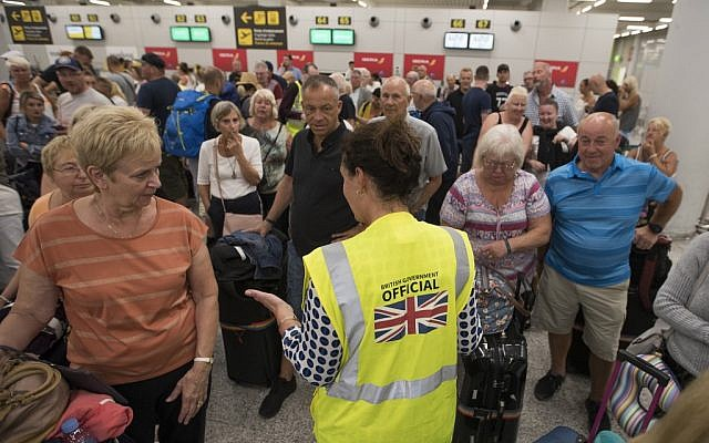 A British Government official speaks with passengers of the British travel group Thomas Cook at Son Sant Joan airport in Palma de Mallorca on September 23, 2019. (JAIME REINA / AFP)