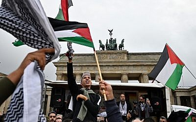 People wave Palestian flags at the Brandenburg Gate during a pro-Palestinian rally in Berlin on September 25, 2019. (Tobias Schwarz/AFP)