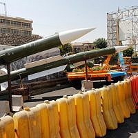 An Iranian woman looks at Taer-2 missile during a street exhibition by Iran's army and paramilitary Revolutionary Guard celebrating 'Defense Week' marking the 39th anniversary of the start of 1980-88 Iran-Iraq war, at the Baharestan Square in Tehran, on September 26, 2019. (STRINGER/AFP)