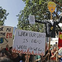 Activists and demonstrators hold placards as they take part in a Global Climate Strike in Tel Aviv on September 27, 2019, against inaction on climate change. (AHMAD GHARABLI / AFP)