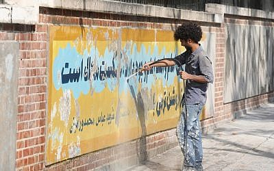 A worker uses a water jet cleaner to erase a mural painting on the wall of the former US embassy in the Iranian capital Tehran on September 29, 2019. (ATTA KENARE / AFP)